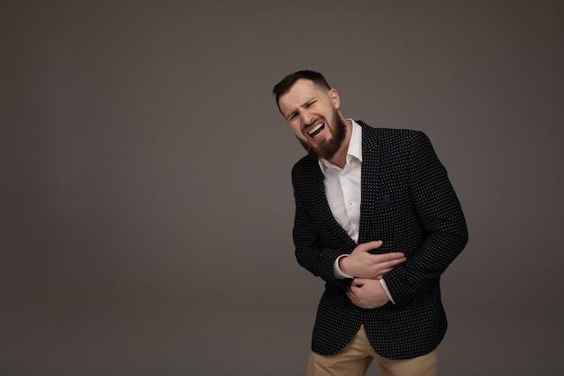 Zakenman die zijn maag pijn op grijze muur houdt. Premium Foto