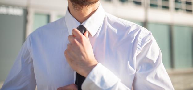 Zakenman die zijn stropdas aanpast Premium Foto
