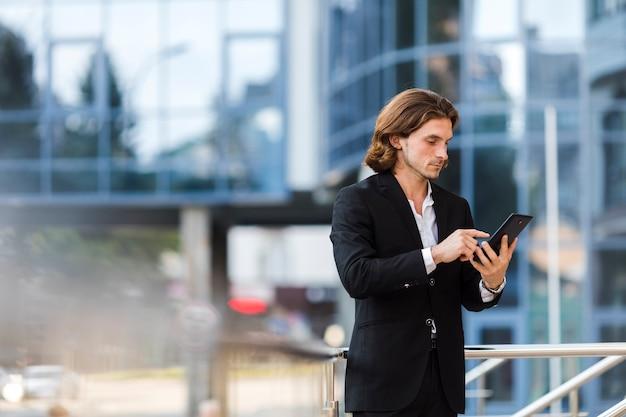 Zakenman die zijn tablet in openlucht gebruikt Gratis Foto