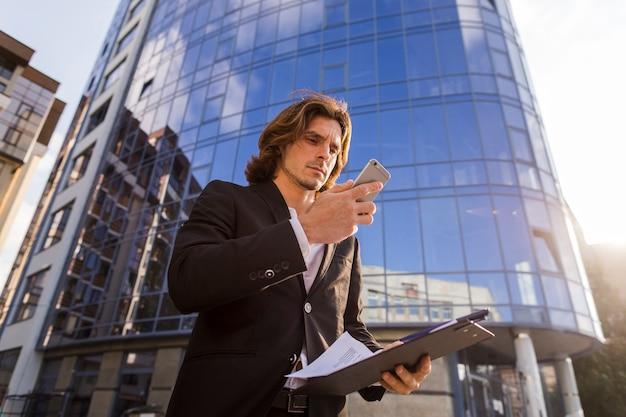 Zakenman die zijn telefoon voor een gebouw met behulp van Gratis Foto
