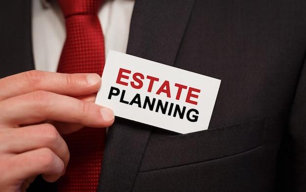 Zakenman een kaart met tekst estate planning in de zak zetten Premium Foto