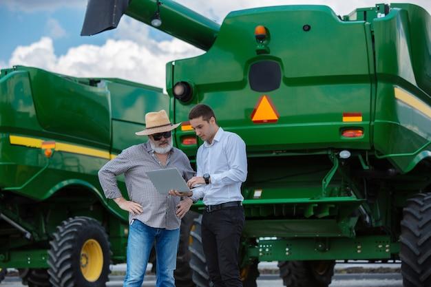 Zakenman en boer met tractoren Gratis Foto