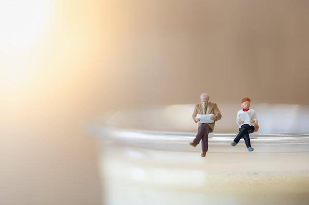 Zakenman en vrouw zitten en lezen boek op de top van plastic kopje ijs koffie latte. Premium Foto