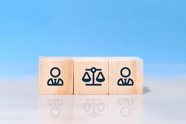 Zakenman en wet pictogrammen op houten kubussen tegen blauwe achtergrond. concept van rechtszaak, gerechtelijk conflict, geschil of vervolging in het bedrijfsleven Premium Foto