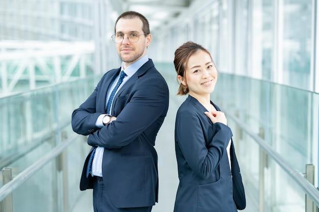 Zakenman en zakenvrouw staan rug aan rug in het gebouw Premium Foto