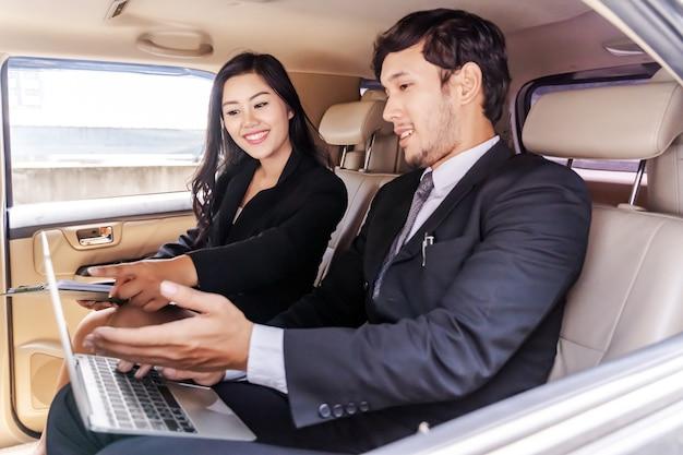 Zakenman en zakenvrouw zittend in de auto, die op laptop werkt, altijd en overal werken Premium Foto