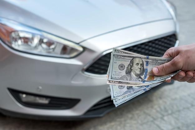 Zakenman geeft geld om een auto te huren voor zomervakantie. financieel concept Premium Foto