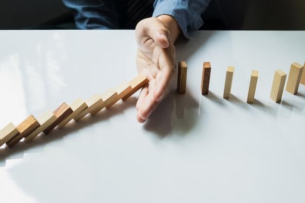 Zakenman hand stoppen domino's voortdurend omgekoppeld of risico met copyspace Gratis Foto