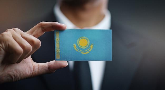 Zakenman holding card van de vlag van kazachstan Premium Foto