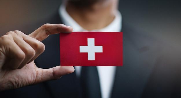Zakenman holding card van de vlag van zwitserland Premium Foto