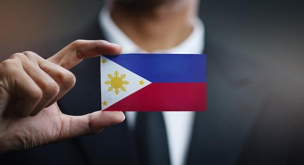 Zakenman holding card vlag van filipijnen Premium Foto