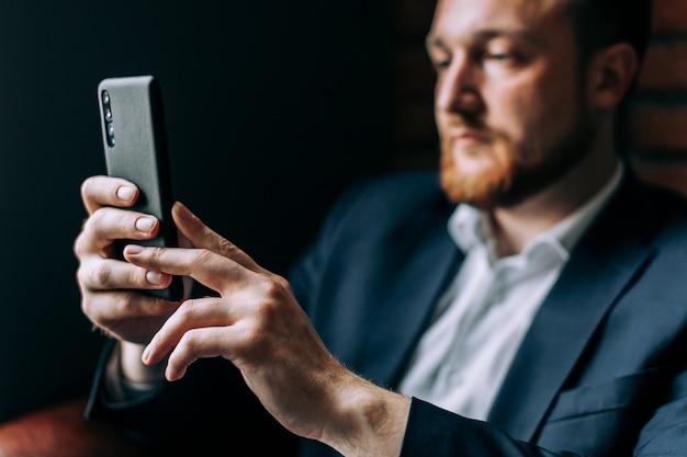 Zakenman in een pak zittend in een stoel met een smartphone en praten over de videoverbinding. Premium Foto