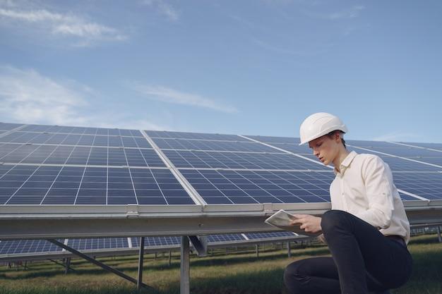 Zakenman in een witte helm in de buurt van zonne-batterij Gratis Foto
