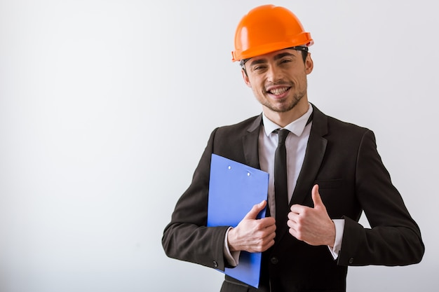 Zakenman in klassiek pak en oranje helm. Premium Foto