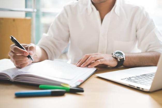 Zakenman in wit overhemd die aan bureaulijst werken Premium Foto