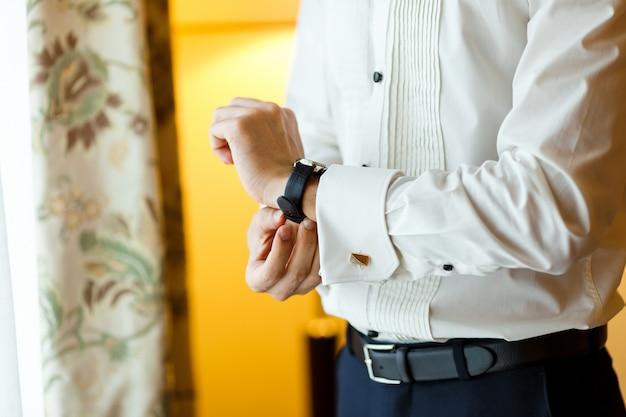 Zakenman in wit overhemd, zwarte lederen riem en manchetknopen die zijn dure horloge dragen Premium Foto