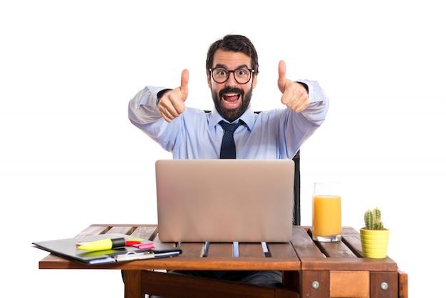 Zakenman in zijn kantoor met duim omhoog Gratis Foto