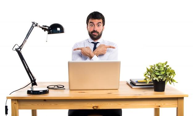 Zakenman in zijn kantoor wijst naar de laterals die twijfels hebben Gratis Foto