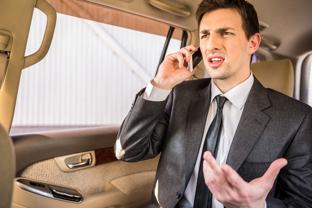 Zakenman in zijn luxe auto en praten over de telefoon. Premium Foto
