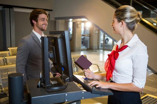 Zakenman interactie met vrouwelijk luchthavenpersoneel bij de incheckbalie Gratis Foto