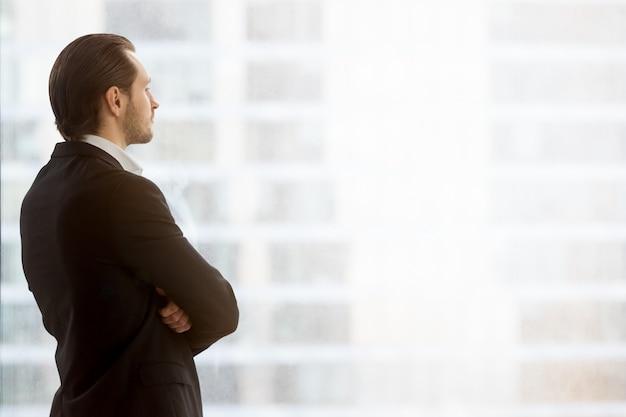 Zakenman kijkt dreamily in venster op kantoor Gratis Foto