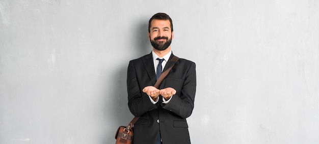 Zakenman met baardholding copyspace denkbeeldig op de palm om een advertentie op te nemen Premium Foto