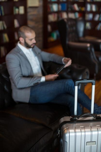 Zakenman met behulp van digitale tablet in wachtruimte Gratis Foto