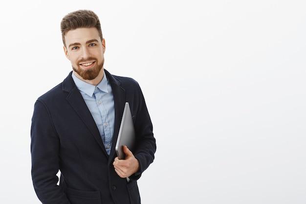 Zakenman met blauwe ogen en baard staan zelfverzekerd in formeel pak met laptop in de hand starend tevreden en zelfverzekerd, ambitieus en succesvol Gratis Foto