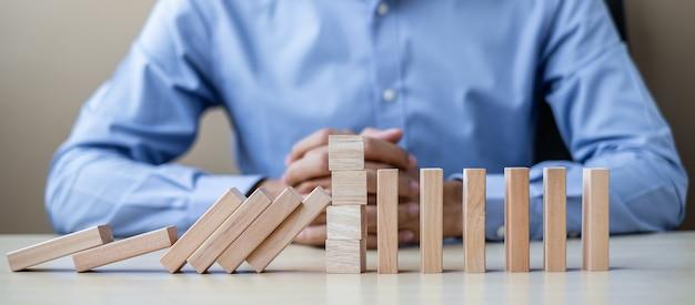 Zakenman met houten blokken of dominostenen. bedrijf Premium Foto