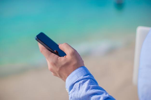 Zakenman met telefoon in hand op een tropisch strand Premium Foto