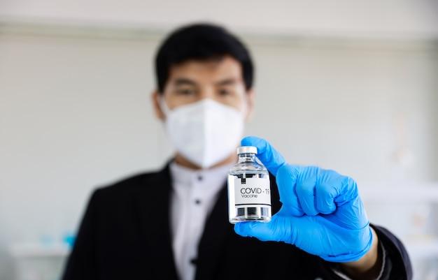 Zakenman met vaccin covid-19 bij de hand Premium Foto