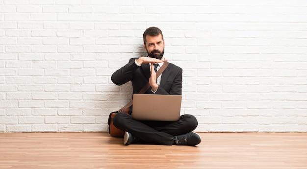 Zakenman met zijn laptop zittend op de vloer stop gebaar maken met haar hand om een daad te stoppen Premium Foto