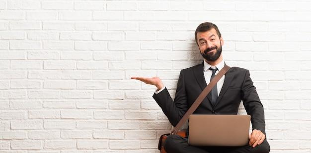 Zakenman met zijn laptop zitting op de vloer die copyspace denkbeeldig op de palm houdt om een advertentie in te voegen Premium Foto