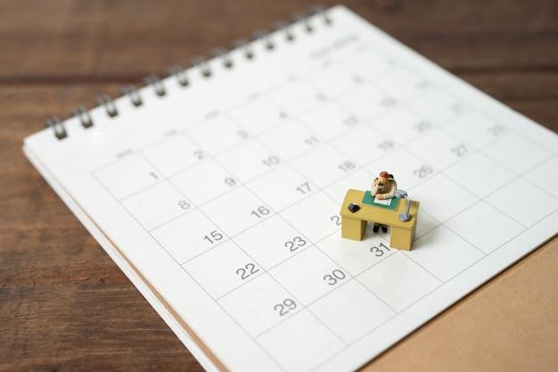 Zakenman miniatuur op kalender Premium Foto