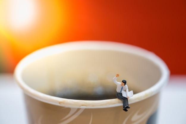 Zakenman miniatuurcijfers zitten en krantendocument kop hete zwarte koffie lezen. Premium Foto