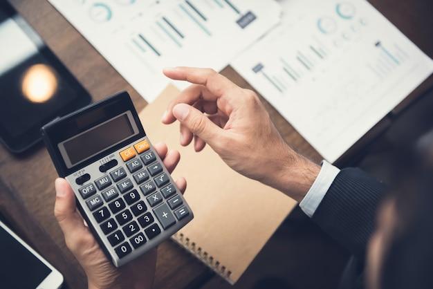 Zakenman of financieel adviseur die calculator gebruiken die gegevens berekenen en analyseren Premium Foto