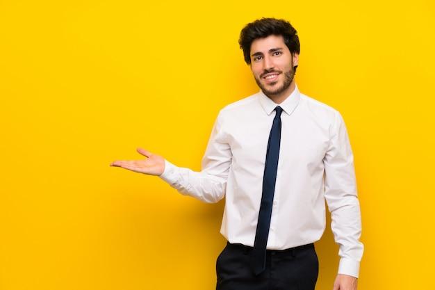 Zakenman op geïsoleerde gele holding copyspace denkbeeldig op de palm Premium Foto