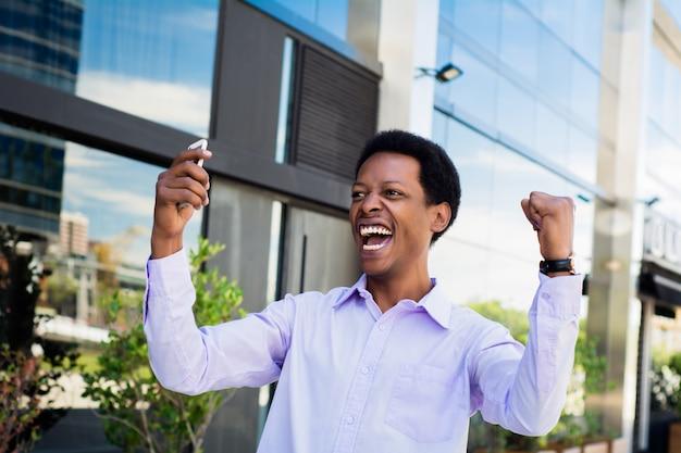 Zakenman opgewonden kijken naar mobiele telefoon. Premium Foto