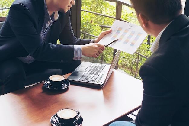 Zakenman twee die hun grafiek in koffiewinkel bespreken Gratis Foto