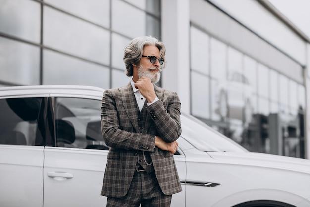 Zakenman van middelbare leeftijd in een autosalon Gratis Foto
