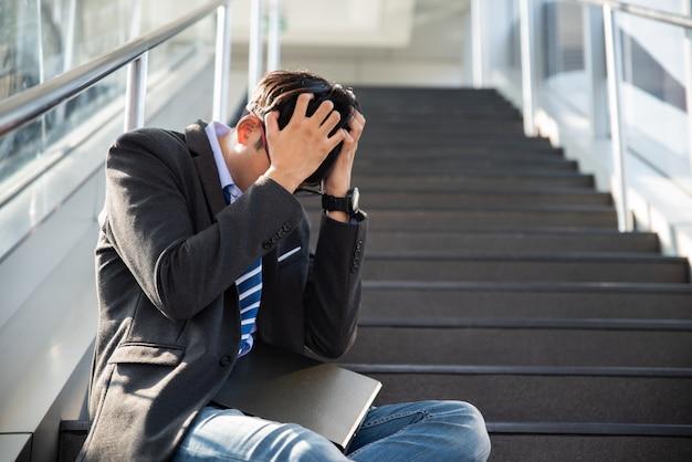 Zakenman verloren in depressie huilen zittend op trappen. benadrukt werkloos concept. Premium Foto