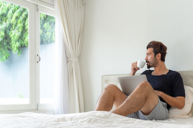 Zakenman voelt zich gelukkig koffie te drinken tijdens het werk op kantoor aan huis Gratis Foto