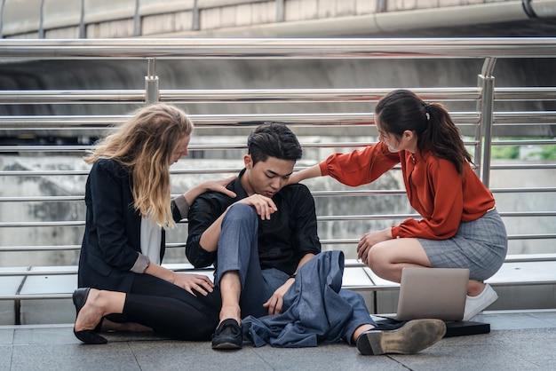 Zakenman zittend op de vloer terwijl zijn vrienden hem steunen Premium Foto