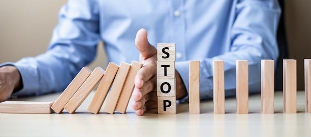 Zakenmanhand die dalende houten blokken of domino's tegenhouden Premium Foto