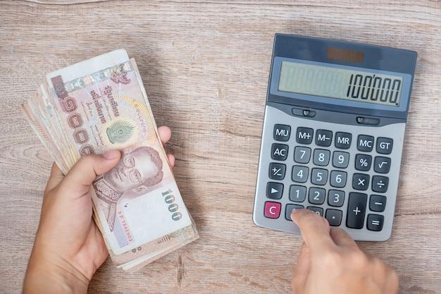 Zakenmanhand die de thaise stapel van het bahtbankbiljet houden en calculator gebruiken. Premium Foto
