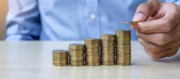 Zakenmanhand die gouden muntstuk op het kweken van geldtreden zet Premium Foto