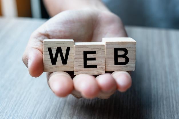 Zakenmanhand die houten kubusblok met web bedrijfswoord houden. website-, netwerk-, database- en marketingconcepten Premium Foto