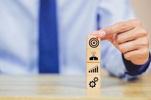 Zakenmanhand die houtsnede met van het bedrijfs pictogramdoel strategie rangschikken. Premium Foto