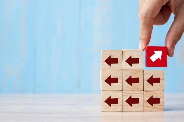 Zakenmanhand die of rood blok met verschillende richting van pijl plaatsen trekken op lijstachtergrond. bedrijfsgroei, verbetering, strategie, succesvol, anders en uniek Premium Foto