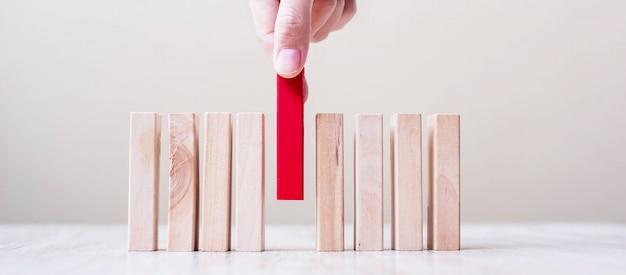 Zakenmanhand die of rood houten blok op lijst plaatsen trekken. bedrijfsplanning, risicobeheer, oplossing, leider, strategie, verschillende en unieke concepten Premium Foto